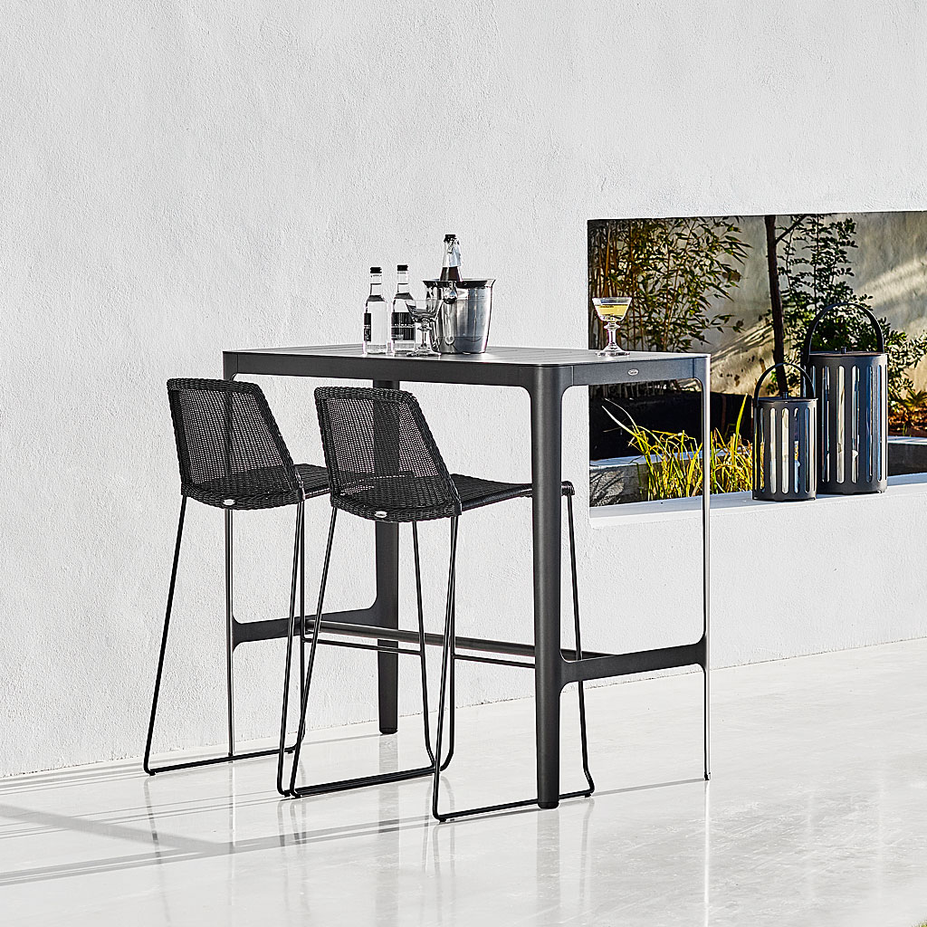 Black Breeze Modern Bar Stool & Cut Bar Table On Terrace. Contemporary Outdoor Bar Chair & Hospitality Outdoor Bar Furniture In Luxury Quality Garden Furniture Materials Designed By Strand+Hvass For Cane-Line Modern Garden Furniture.