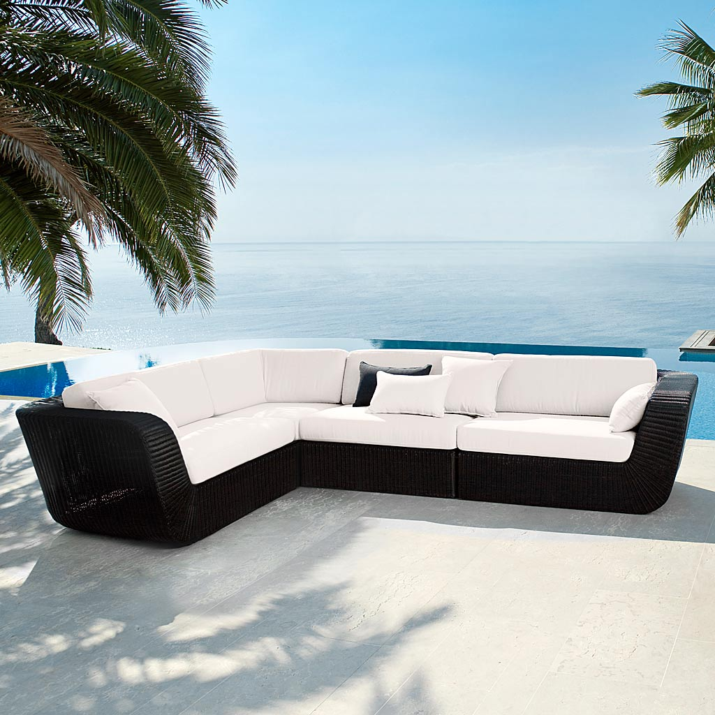 Black Savannah Modular Rattan Garden Sofa With White Cushions. All-Weather Woven Outdoor Sofa In High Quality Garden Furniture Materials By Cane-line Modern Garden Furniture.